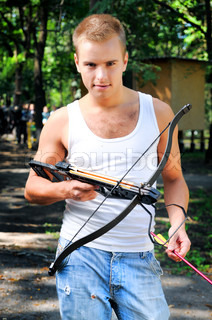 A young man with a crossbow and arrows in the woods
