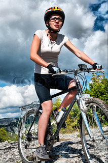 athletic girl rides a bicycle on a mountain road