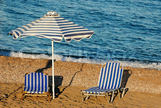 Sun beds and umbrellas on the beach - Rhodes, Greece