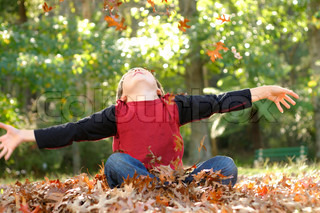 A boy throws fallen leaves up into the air There is some motion in the hands and falling leaves