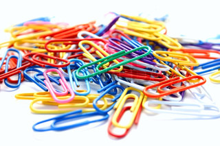 Many colorful paper clips on white background