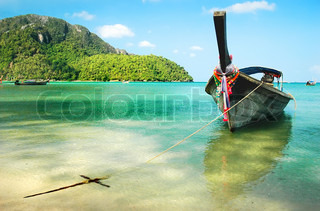 Wooden boat moored on the beach of the island of Phi Phi, Thailand