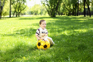 Little boy in the summer park playing with a ball