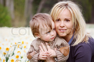 A young mother with her son and a bed of daffodils