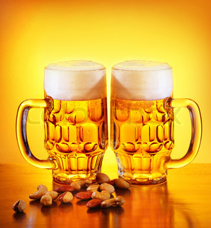 Glass of cold beer drink and nuts isolated on yellow warm background, festival of beer, oktoberfest autumn holiday