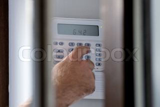 This photograph represent a human hand arming a burglar alarm system The view is similar as a a spy view this situation