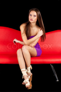 Sexy young brunette lady on red sofa