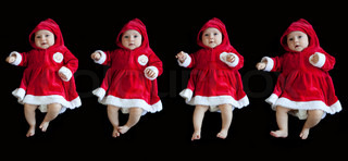 dancing babies in christmass dresses isolated on black