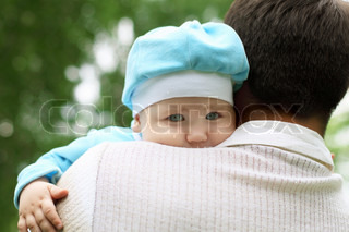 Father with holding his baby boy outside in the park