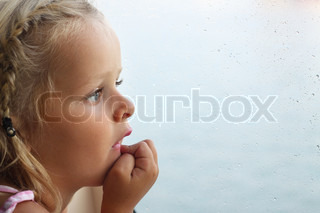 Little girl looking out of window covered with raindrops