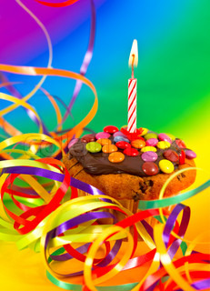 birthday cupcake with burning candle on multicolored decoration