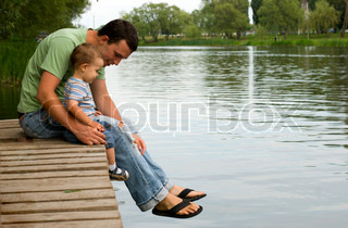 Father and son sitting near a river