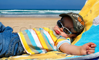 Portrait of one year old boy sleeping on beach