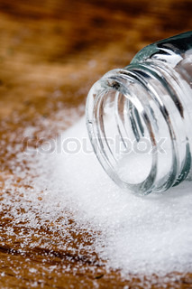 salt in glass container closeup on wooden background