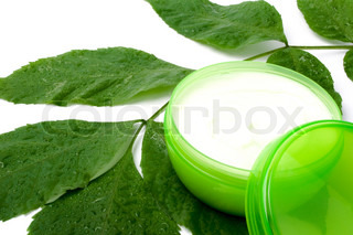 face cream with green leaf on white background