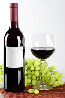 Bottle and glass of red wine and grapes in back isolated on white background
