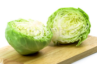 two halves of green cabbage on wooden chopping board