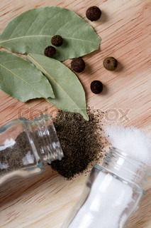 spices: pepper, salt and bay leaves closeup on wooden background