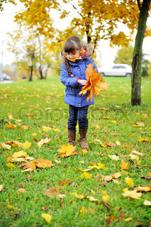 Toddler girl in blue coat picking up leaves on a meadow