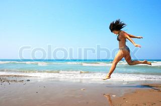 Jumping brunette pige på stranden