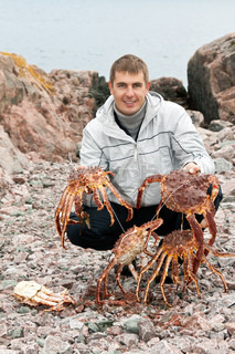 man with crabs in the Barents Sea coast, after a successful fishing