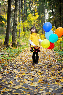 Child girl with colorful balloons walking alone in autumn forest