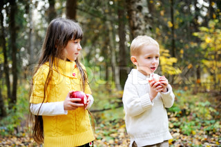 Little boy and child girl eating apples while walking in forest