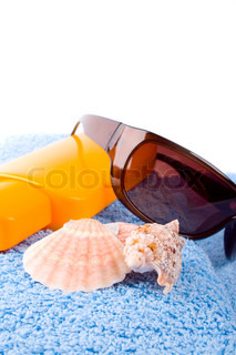 towel, shells, sunglasses and lotion closeup on white background