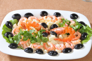 Shrimp salad in pineapple pieces, olives and parsley