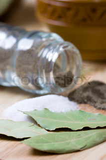 spices: pepper, salt, bay leaves closeup on wooden background