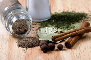 spices: pepper, cinnamon, salt, bay leaves and herbs closeup on wooden background