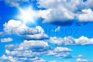 Blue sky background with fluffy clouds & bright sunshine