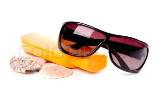 sunglasses, shells and lotion closeup on white background