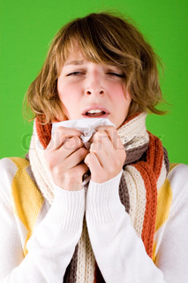 portrait of a cold girl sneezes on green background
