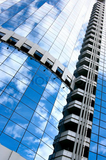 Architectural background with building and sky reflction in the windows