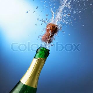 Flasche Sekt mit Spritzern auf blauem Hintergrund