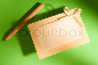 Greeting card and pencil isolated on the green background