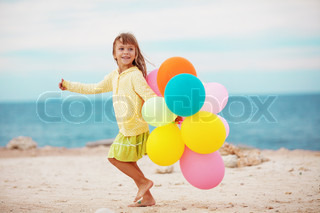 Portrait of little girl playing with air balloons at the beach