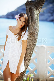 Portrait of beautiful brunette woman with lily in her hair posing over sea view