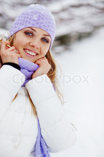 Portrait of cute young woman walking outdoors in winter