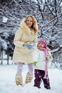 Portrait of young woman with kid girl playing snowballs in winter