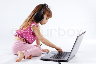 Portrait of funny modern child playing with computer and listening to music in headphones