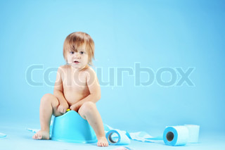 Studio shot of funny toddler sitting on potty chair and playing with toilet paper