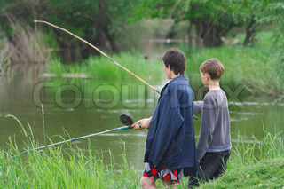Mother and son catch the fish on the river shore
