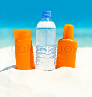 drink water and sun protection cream on sand beach background