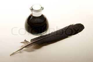 Feather and ink bottle isolated on paper background