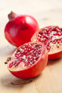 sliced pomegranate on wooden table