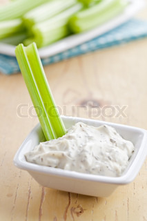 photo shot of green celery sticks with tasty dip