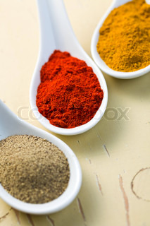 various spicy powder on wooden table