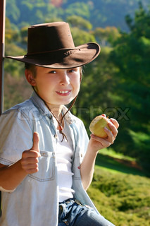 Friendly mountain boy sitting on the balcony in the afternoon eating fresh fruit and giving the thumbs up